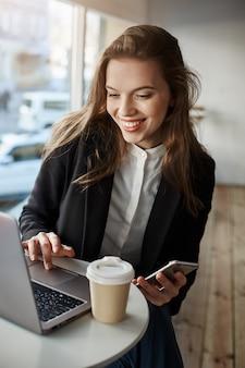 Retrato de una mujer encantadora y elegante en un café, navegando en la red a través de una computadora portátil, sosteniendo un teléfono inteligente y bebiendo té, usando wifi gratis y disfruta del tiempo libre