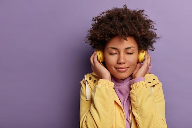 Retrato de mujer encantadora meloman usa auriculares electrónicos