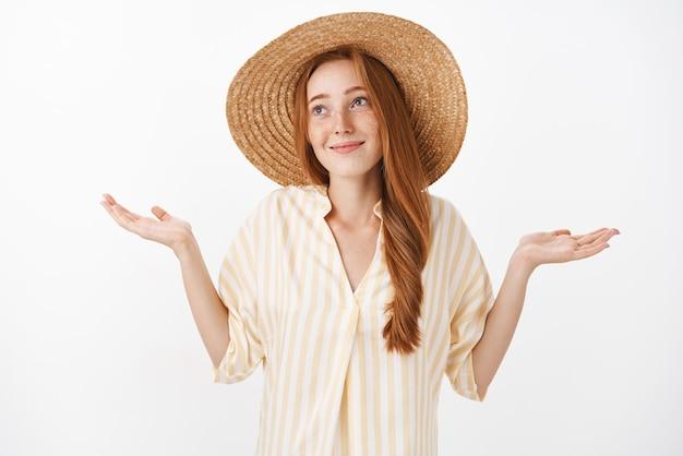 Retrato de mujer encantadora, optimista y despreocupada con cabello pelirrojo y pecas en un lindo sombrero de paja y una blusa amarilla que hace que el hombro se encoja con las manos extendidas y una mirada inocente