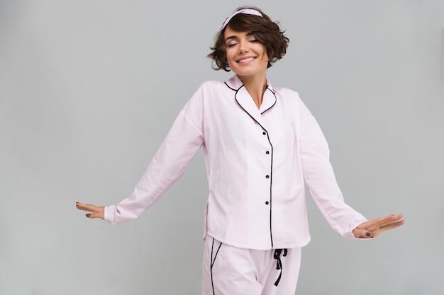 Retrato de una mujer encantadora en pijama estirando sus manos