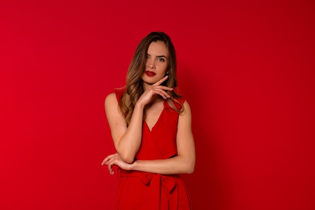 Retrato de mujer encantadora sonriente en vestido rojo posando