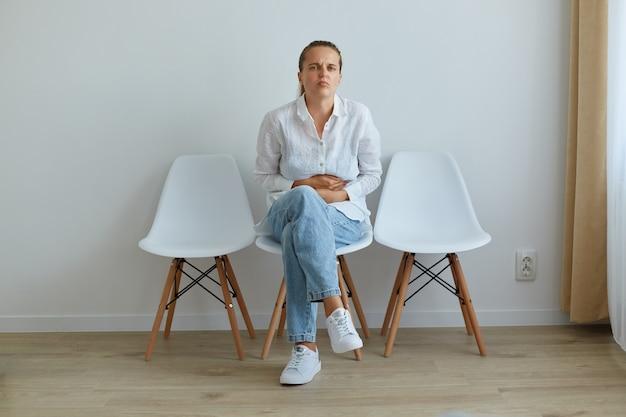 Retrato de mujer enferma con cabello oscuro y cola de caballo, vestida con camisa blanca y jeans, sentada en una silla en la cola para el médico en la clínica, que sufre de un terrible dolor de estómago.