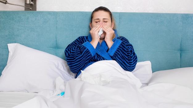Retrato de mujer enferma con frío soplando su nariz que moquea