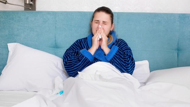 Retrato de mujer enferma con gripe que moquea la nariz en un pañuelo de papel.