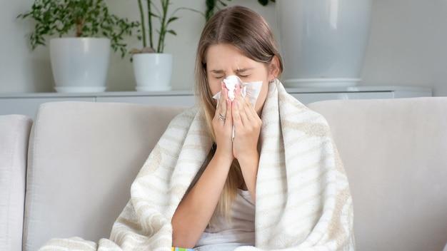 Retrato de mujer enferma con secreción nasal sonándose la nariz en un pañuelo de papel