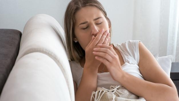 Retrato de mujer enferma con virus acostado en el sofá y tosiendo