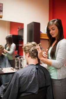 Retrato de una mujer enfocada cortando el cabello de un hombre
