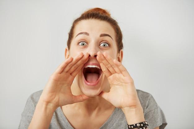 Retrato mujer enojada gritando, boca abierta, histérica pared gris aislada