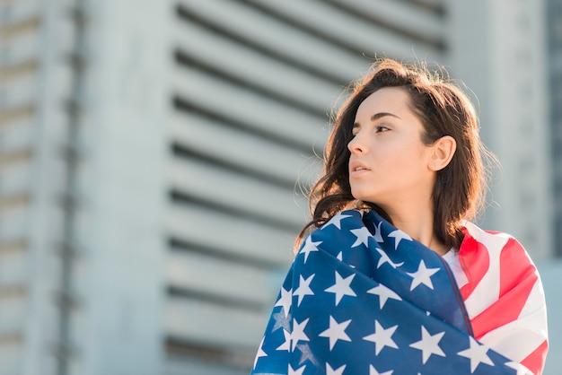 Retrato de mujer envolviéndose en la bandera de estados unidos mirando a otro lado