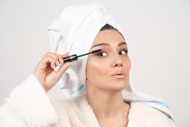 Retrato de mujer envuelta en una toalla blanca aplicando rímel.
