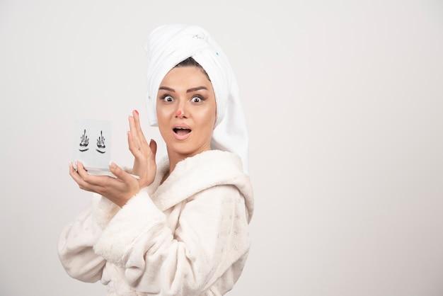 Retrato de mujer envuelta en una toalla blanca con paleta de sombras de ojos