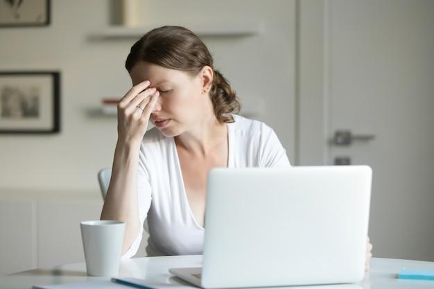 Retrato de una mujer en el escritorio con la computadora portátil, la mano en la frente
