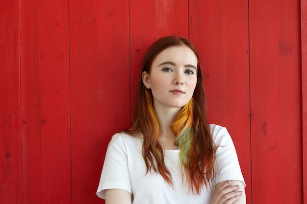 Retrato de mujer estudiante pelirroja confiada con hebras de colores en el cabello vestida con camiseta blanca mirando