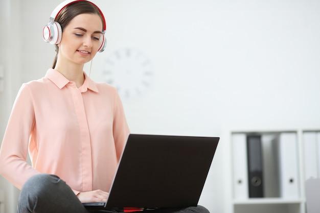 Retrato de una mujer estudiante que estudia y escucha música en línea