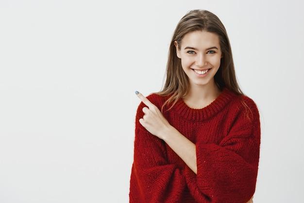 Retrato de mujer europea encantadora positiva en elegante suéter rojo suelto apuntando a la esquina superior izquierda y sonriendo amigable, diciendo buenos consejos o artículo publicitario cerca de fondo gris