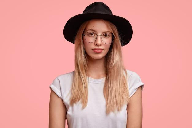 Retrato de mujer europea con estilo lleva gafas y sombrero negro de moda, tiene expresión seria