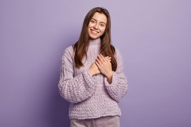 Retrato de mujer europea joven feliz mantiene las manos en el pecho, muestra el gesto del corazón, expresa gratitud, estar agradecido, modelos contra la pared púrpura lenguaje corporal. monocromo. gente y devoción