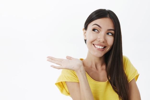 Retrato de mujer europea linda complacida alegre con cabello oscuro en camiseta amarilla de moda inclinándose hacia la izquierda