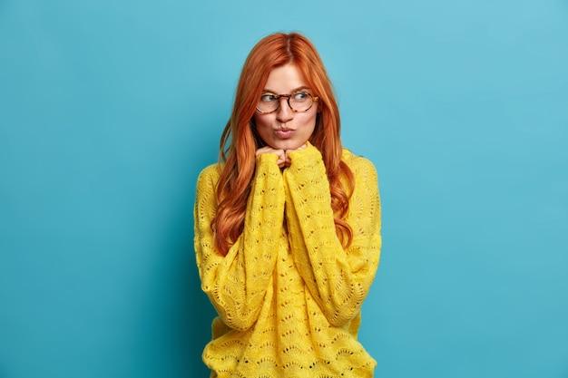 Retrato de mujer europea pelirroja encantadora mantiene las manos debajo de la barbilla y los labios redondeados sueña con algo romántico lleva gafas transparentes y suéter amarillo.