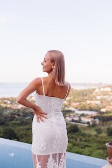 Retrato de mujer europea en vestido de novia con collar y anillo.