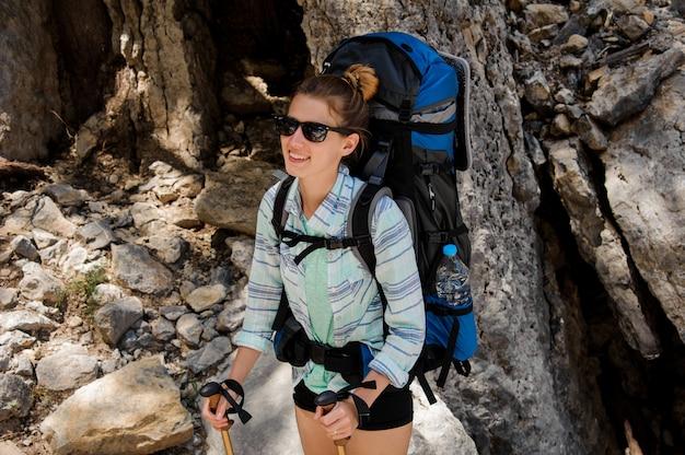 Retrato de mujer excursionista en gafas de sol con mochila