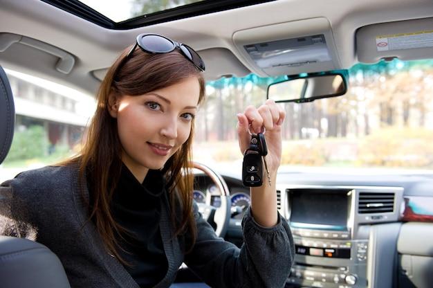 Retrato de mujer de éxito feliz con llaves del coche nuevo
