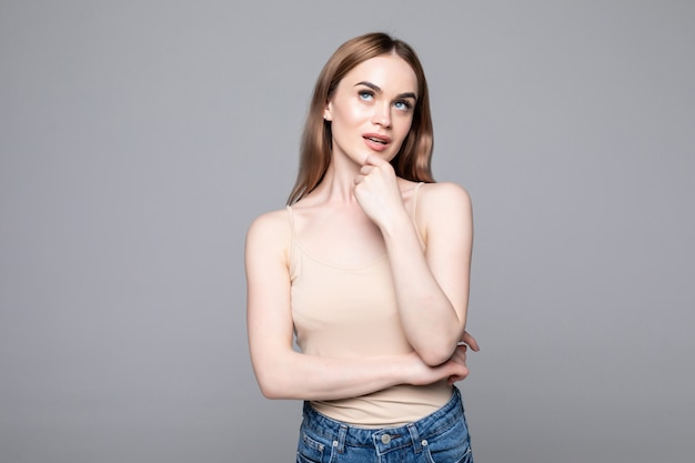 Retrato de mujer exitosa mirando a un lado y sosteniendo el dedo en la mejilla mientras sonríe aislado sobre pared gris