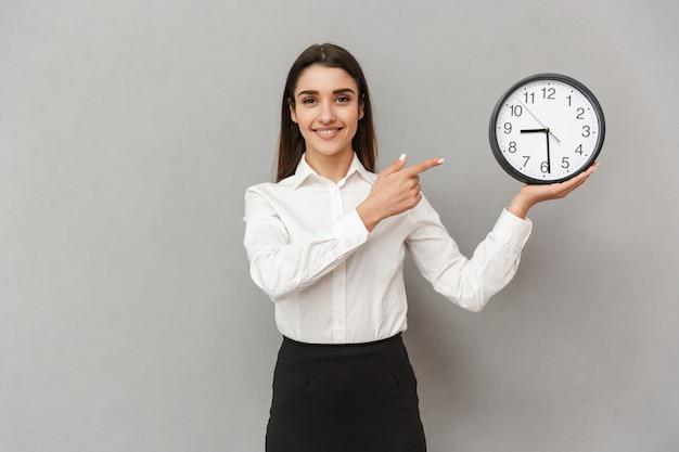 Retrato de mujer exitosa sonriente en camisa blanca y falda negra que señala el dedo en el reloj redondo sosteniendo en la mano, aislado sobre la pared gris