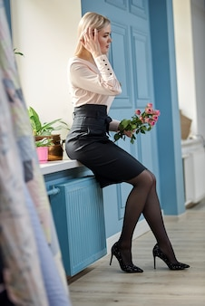 Retrato de mujer en falda negra y blusa con flores. linda mujer con ramo de flores en sus manos