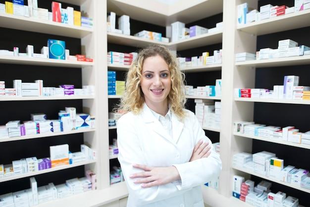 Retrato de mujer farmacéutica en la farmacia de pie delante de los estantes con medicamentos