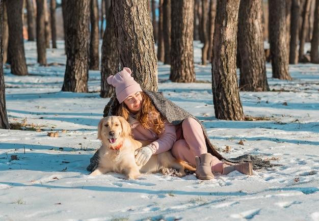 Retrato de una mujer feliz abrazando a su perro golden retriever cubierto junto con un plaid en un bosque nevado.
