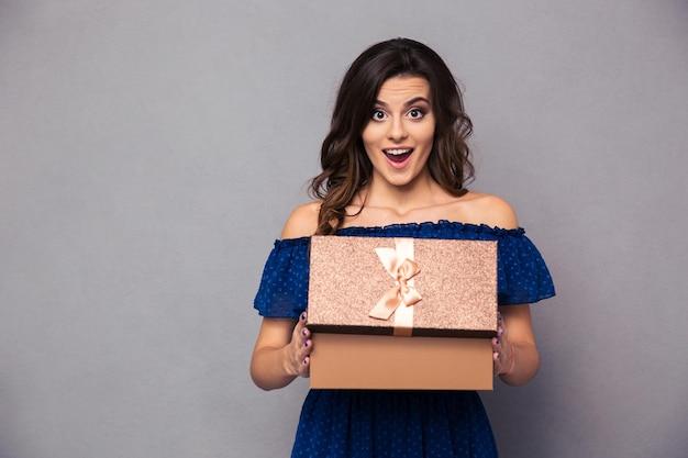 Retrato de una mujer feliz abriendo caja de regalo y sobre pared gris
