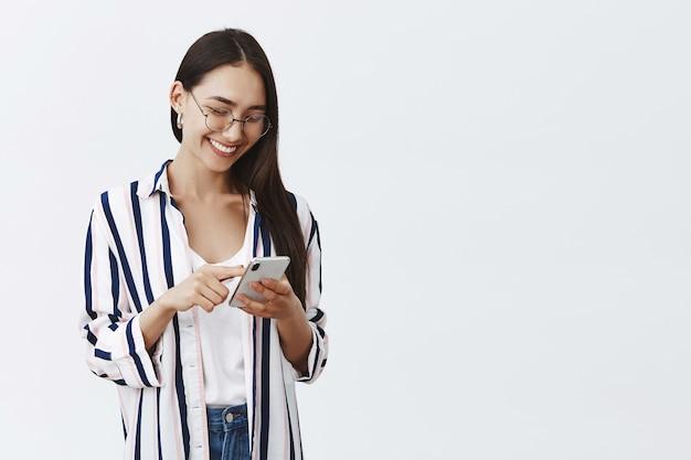 Retrato de mujer feliz atractiva y elegante con gafas y blusa a rayas, alimentación de desplazamiento mientras usa el teléfono inteligente, leyendo un artículo divertido en internet