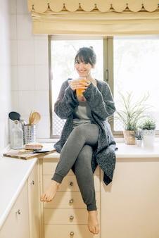 Retrato de una mujer feliz bebiendo jugo en la cocina