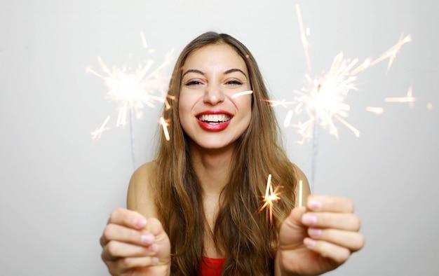 Retrato de mujer feliz con bengalas encendidas en tiro de estudio