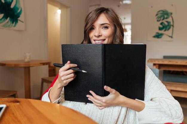 Retrato de una mujer feliz con bloc de notas de portada en blanco