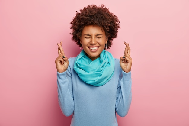 Retrato de mujer feliz con cabello afro, mantiene los dedos cruzados, cree en la buena suerte, sonríe ampliamente, viste un suéter azul con bufanda