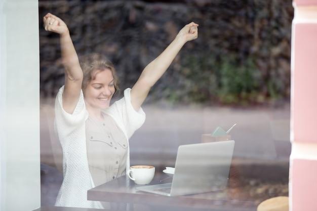 Retrato de mujer feliz en la cafetería celebrando el éxito con sus manos arriba