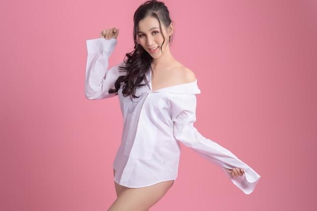 Retrato de mujer feliz con camisa blanca en rosa.
