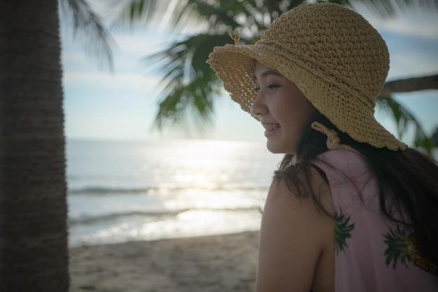 Retrato mujer feliz cara en la playa al atardecer. chica joven en las vacaciones de verano tropicales.