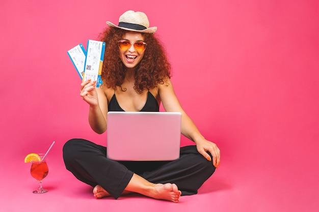 Retrato de mujer feliz en casual sentado en el suelo en posición de loto y sosteniendo un portátil, un cóctel y un billete de avión