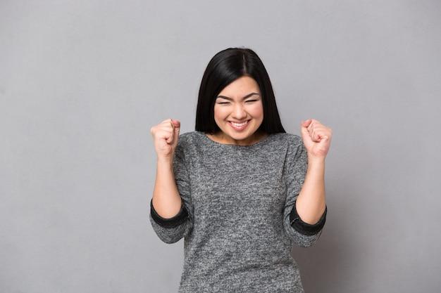 Retrato de una mujer feliz celebrando su éxito sobre la pared gris
