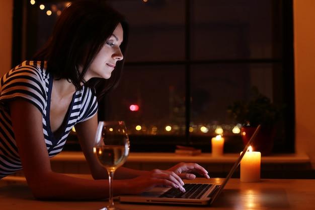 Retrato de mujer feliz con copa de vino mirando la pantalla de la pc