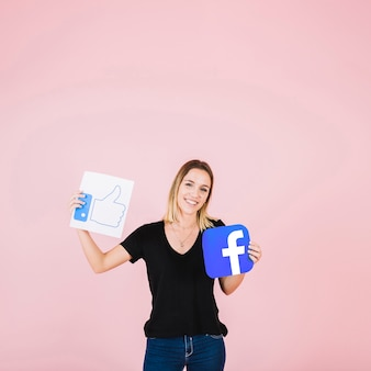 Retrato de una mujer feliz con facebook icono de pulgares arriba