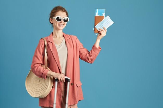 Retrato de mujer feliz en gafas de sol con billetes y pasaporte sonriendo a la cámara de pie contra el fondo azul.