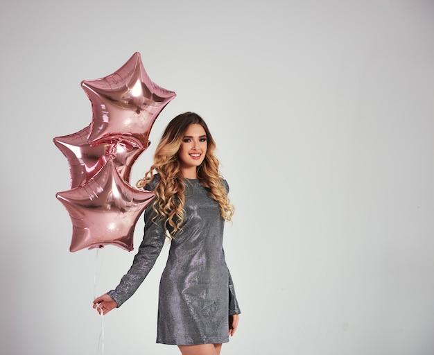 Retrato de mujer feliz con globos en forma de estrella