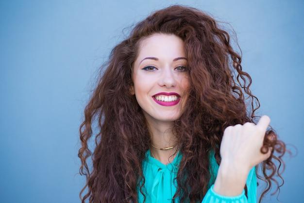 Retrato de una mujer feliz hermosa joven pelirroja en una pared azul