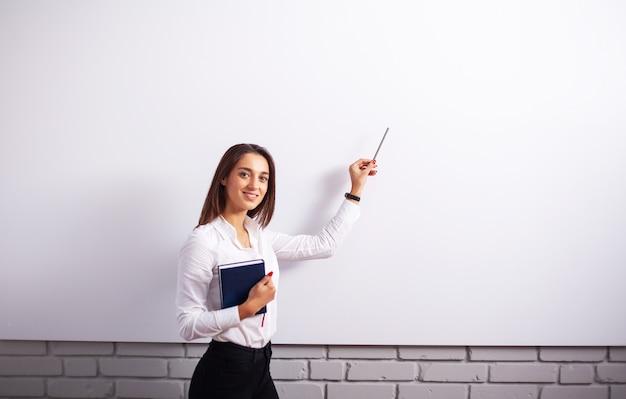 Retrato de mujer feliz joven empresaria cerca de pared blanca