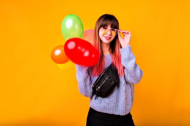 Retrato de mujer feliz joven inconformista mostrando gesto ok y riendo, suéter azul acogedor, gafas de moda y bolso, sosteniendo globos de colores, humor de fiesta.