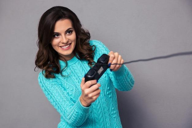 Retrato de una mujer feliz jugando con joystick sobre pared gris